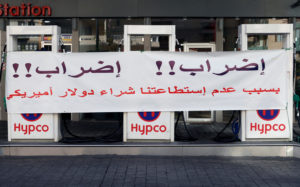 "A banner is seen at a petrol station in Beirut, Lebanon on November 28, 2019. The banner reads: ""Strike!! Strike!! Because we can't buy the U.S. dollar"". Photo by Mohamed Azakir/Reuters"