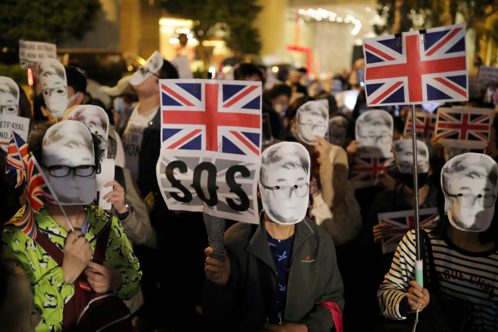 Anti-government protesters wearing masks depicting Simon Cheng, a former British Consulate employee, hold banners as they attend a rally outside the British Consulate General in Hong Kong, China, November 29, 2019. Photo by Marko Djurica/Reuters.