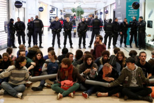 Youth for Climate activists sit-in in front of French police as they block an aisle of the Westfield Les 4 Temps shopping center during a day of protest to denounce the annual Black Friday shopping frenzy at La Defense business and financial district in Puteaux near Paris, France, November 29, 2019. Photo by Gonzalo Fuentes/Reuters,