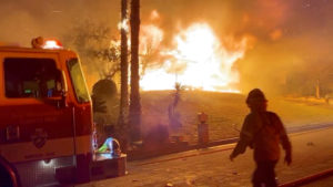 A firefighter passes by a fire engine in front of a burning house during wildfires in San Bernardino, California, on October 31, 2019, in this screen grab obtained from a social media video. 564FIRE via Reuters