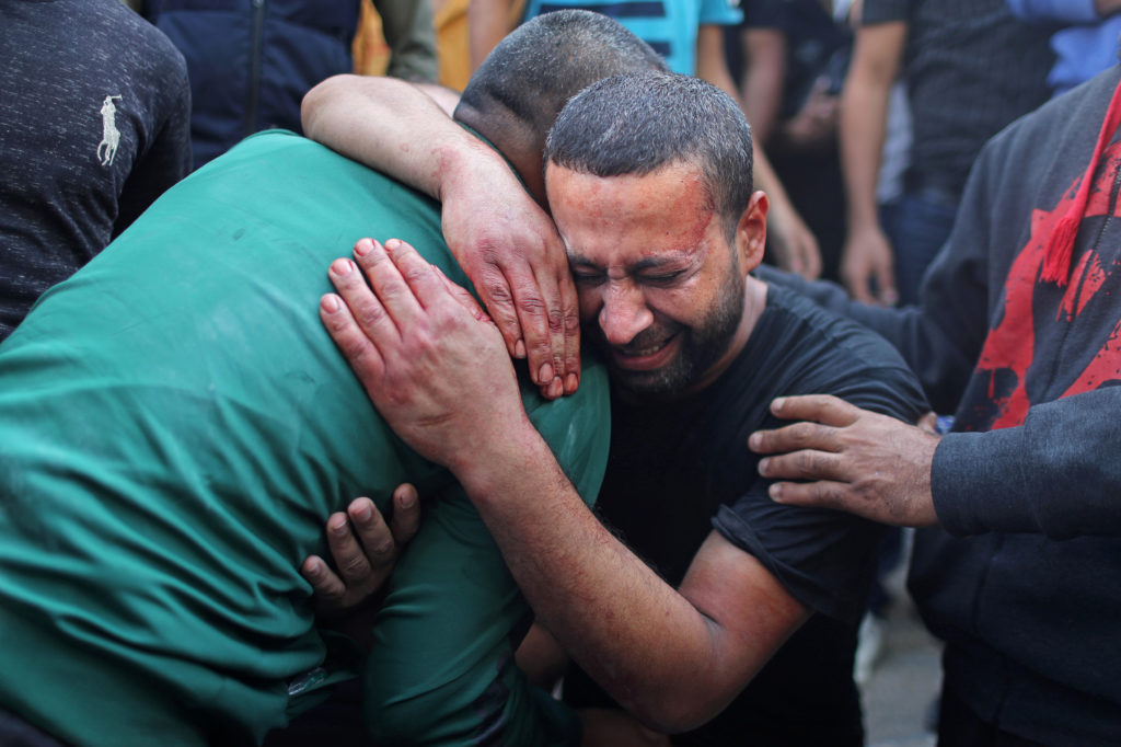 A Palestinian man, stained with the blood of his relative, is comforted as he reacts at Shifa hospital in Gaza City November 13, 2019. Photo by REUTERS/Mohammed Salem