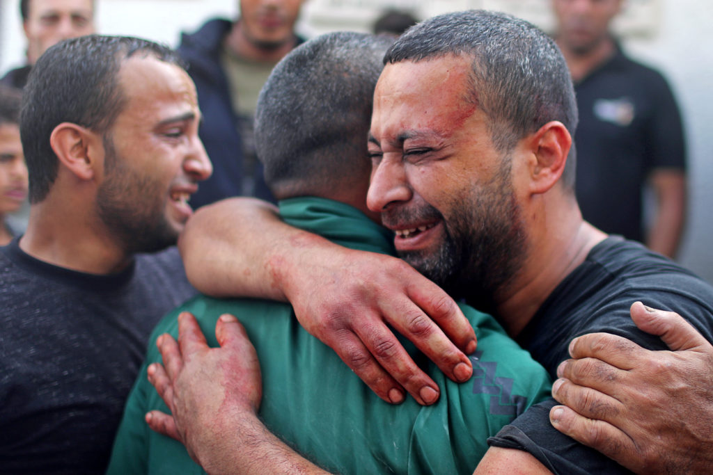 A Palestinian man, stained with the blood of his relative, is comforted as he reacts at Shifa hospital in Gaza City Novemb...