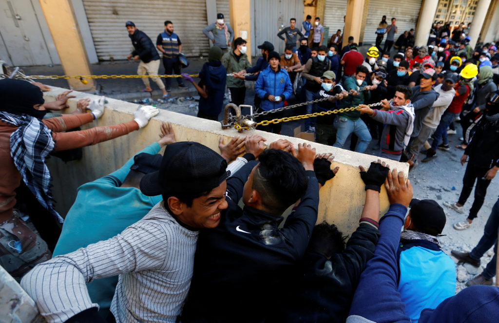 Iraqi demonstrators try to push down a concrete wall during ongoing anti-government protests in Baghdad, Iraq November 21, 2019. Photo by REUTERS/Thaier al-Sudani