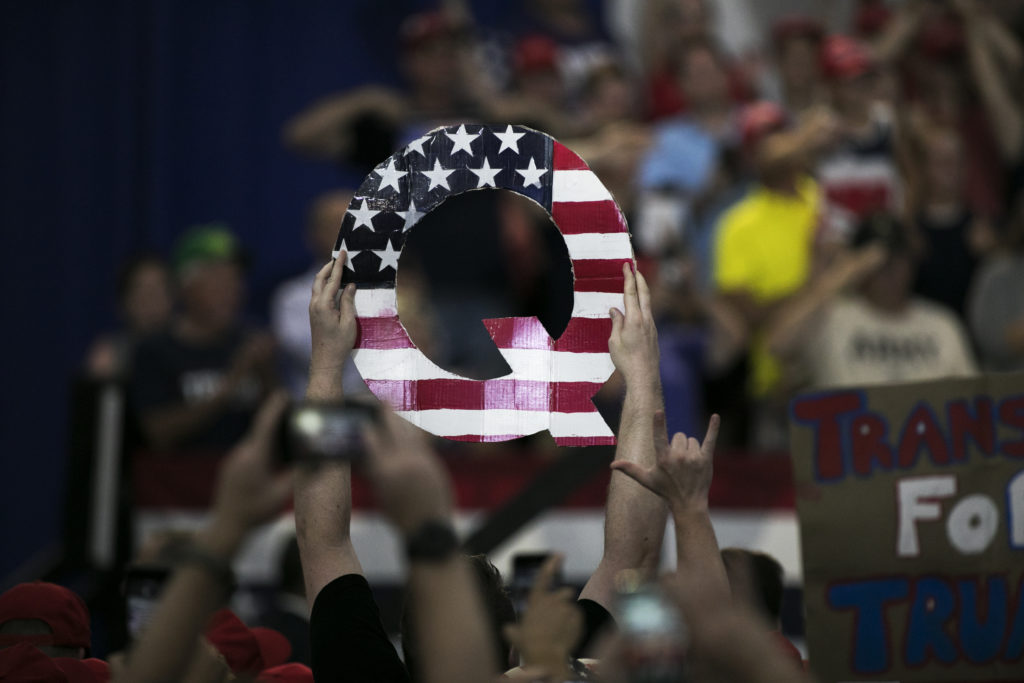 "An attendee holds signs a sign of the letter ""Q"" before the start of a rally with U.S. President Donald Trump in Lewis Center, Ohio, U.S., on Saturday, Aug. 4, 2018. QAnon is a far-right conspiracy theory alleging that President Trump is conducting a purge of non-existent deep state actors from the government. Photo by Maddie McGarvey via Bloomberg / Getty Images"