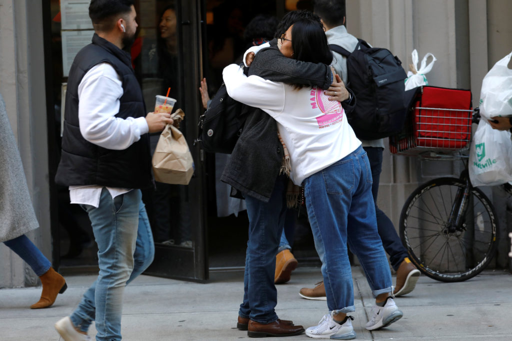 WeWork employees embrace on the sidewalk outside the entrance to the WeWork corporate headquarters in Manhattan, New York, U.S., November 21, 2019. Photo by REUTERS/Mike Segar