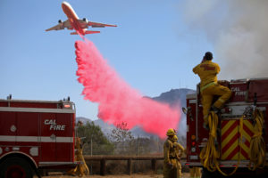 Cal Fire firefighters look on as a plane drops fire retardant on the Maria Fire in Santa Paula, California, on November 1, 2019. Photo by Daniel Dreifuss/Reuters