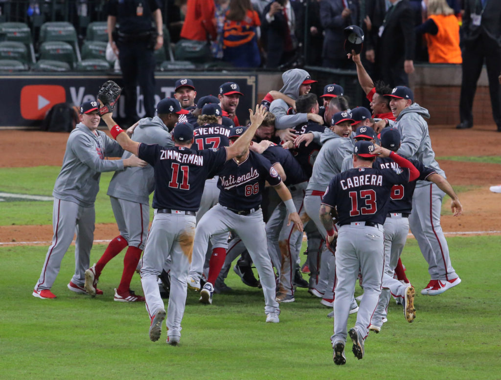 Washington Nationals players celebrate on the field after defeating…