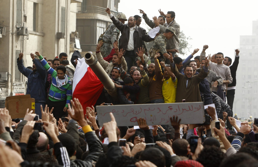 Demonstrators celebrate atop an army tank in Tahrir square during protests in Cairo January 29, 2011. Egyptian President Hosni Mubarak refused on Saturday to bow to demands that he resign after ordering troops and tanks into cities in an attempt to quell an explosion of street protests against his 30-year rule. Photo by Yannis Behrakis/Reuters