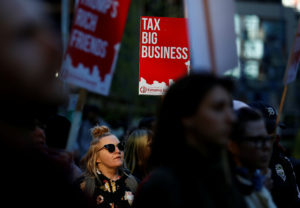 A woman holds a sign supporting the taxation of big businesses during a protest in front of the Amazon Spheres to demand that the city of Seattle tax the largest corporations to help fund affordable housing, according to organizers, in Seattle, Washington, U.S., April 10, 2018. REUTERS/Lindsey Wasson
