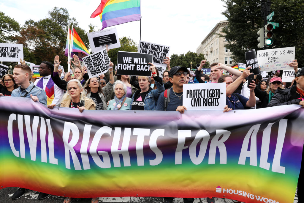 LGBTQ activists and supporters block the street outside the U.S. Supreme Court as it hears arguments in a major LGBT right...