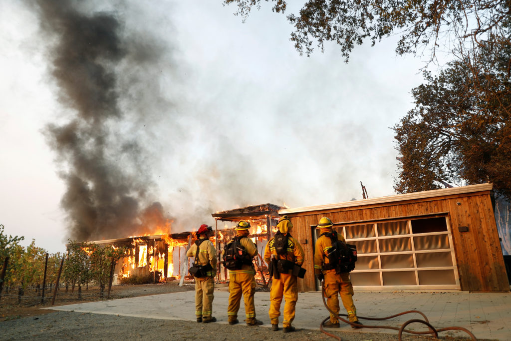 A group of firefighters look on as a house burns during the wind-driven Kincade Fire in Healdsburg, California, U.S. October 27, 2019. Photo by Stephen Lam/Reuters