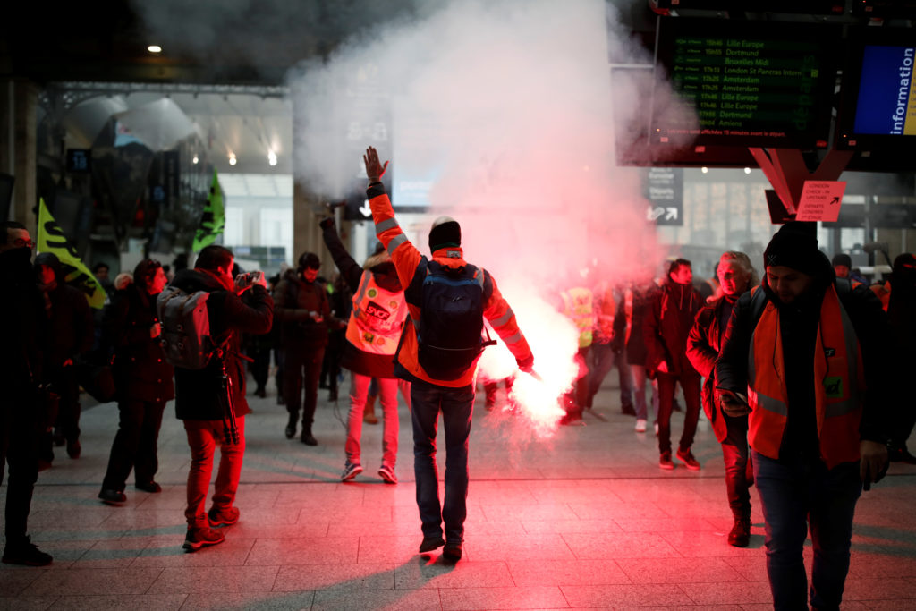 A French SNCF railway worker on strike holds a flare as he walks at Gare du Nord railway station before a demonstration against French government's pensions reform plans in Paris as part of a day of national strike and protests in France, December 5, 2019.  Photo by Benoit Tessier/Reuters