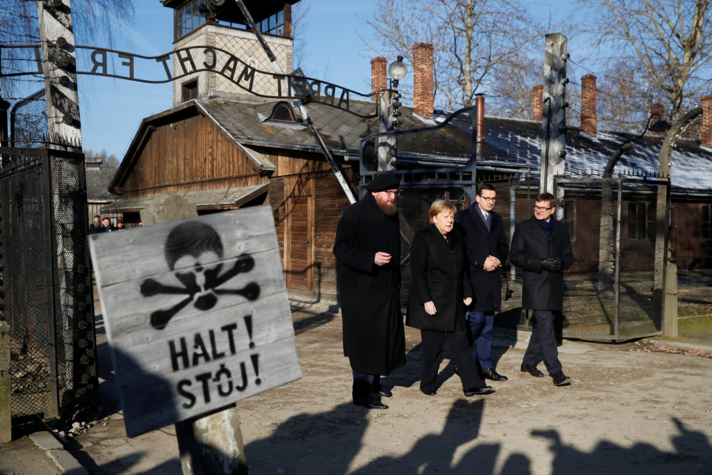 """German Chancellor Angela Merkel, Poland's Prime Minister Mateusz Morawiecki and museum director Piotr Cywinski walk past the """"Arbeit Macht Frei"""" gate at the former Nazi German concentration and extermination camp Auschwitz in Oswiecim, Poland, December 6, 2019. Photo by Kacper Pempel/Reuters"""