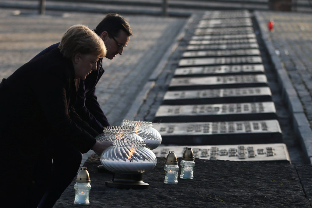 Polish Prime Minister Mateusz Morawiecki and German Chancellor Angela Merkel place candles at the Monument to the Victims at the former Nazi German concentration and extermination camp Auschwitz II-Birkenau near Oswiecim, Poland December 6, 2019. Jakub Porzycki/Agencja Gazeta via REUTERS