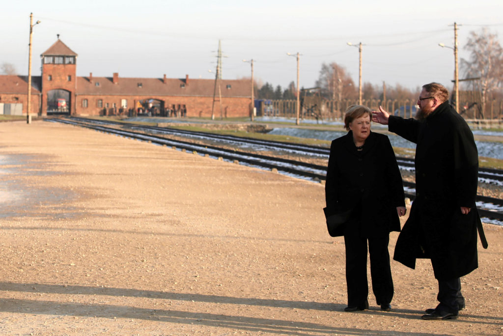 German Chancellor Angela Merkel listens to historian Piotr Cywinski near the Monument to the Victims at the former Nazi German concentration and extermination camp Auschwitz II-Birkenau near Oswiecim, Poland December 6, 2019. Jakub Porzycki/Agencja Gazeta via Reuters