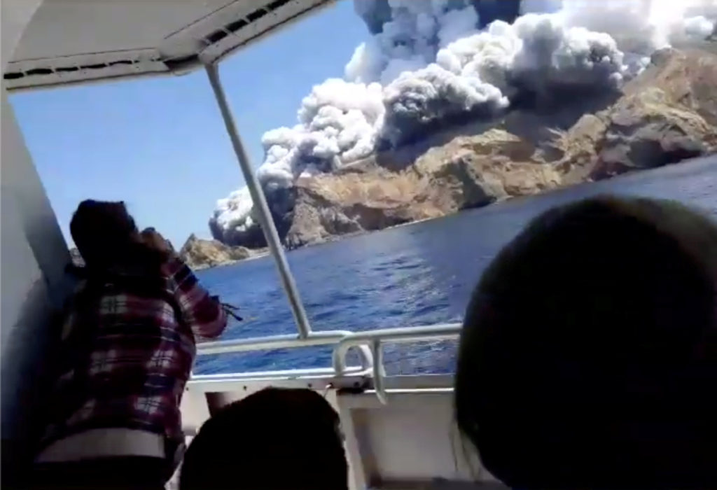People on a boat react as smoke billows from the volcanic eruption of Whakaari, also known as White Island, New Zealand De...