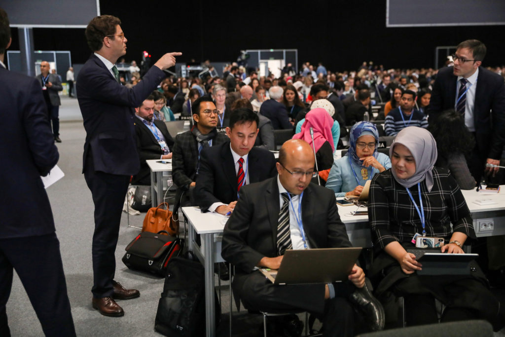 Brazil'sEnvironmentMinister Ricardo Salles talks with other delegation members, ahead of a plenary session during the U....