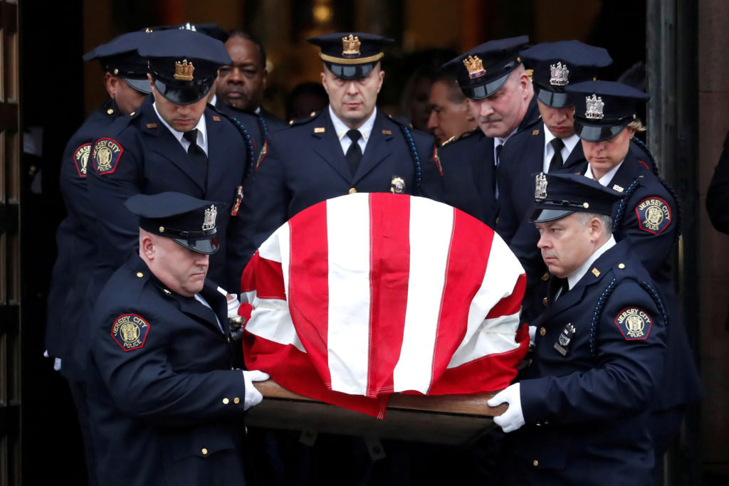 The casket of Jersey City Police Detective Joseph Seals is carried from St. Aedan's Church during his funeral service in J...