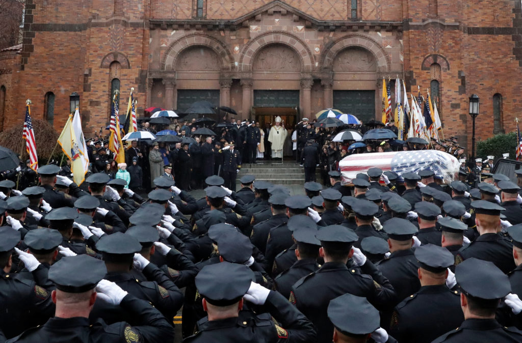 Police officers stand and salute as the casket is carried into the funeral service for Jersey City Police Detective Joseph Seals at St. Aedan's Church in Jersey City, New Jersey, U.S., December 17, 2019. Photo by REUTERS/Shannon Stapleton