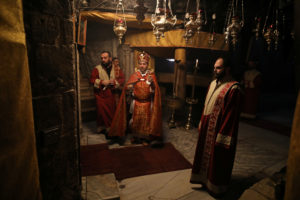 Clergymen pray inside the Church of the Nativity on Christmas eve in Bethlehem, in the Israeli-occupied West Bank December 24, 2019. Photo by Ammar Awad/Reuters