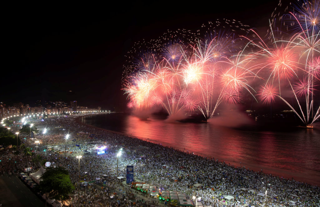 People watch as fireworks explode over Copacabana beach during New Year celebrations in Rio de Janeiro, Brazil January 1, 2020. Photo by Ueslei Marcelino/Reuters