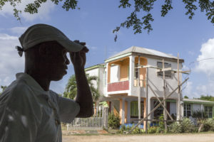 On 7 November 2019, on the island of Barbuda, James Gerald stands in front of his family's home, which was damaged by Hurricane Irma in September 2017. James and his family — mother Corine, son James Jr., 13, and daughter Jerrene, 11 — were evacuated to Antigua from Barbuda following Hurricane Irma. Photo courtesy: UNICEF