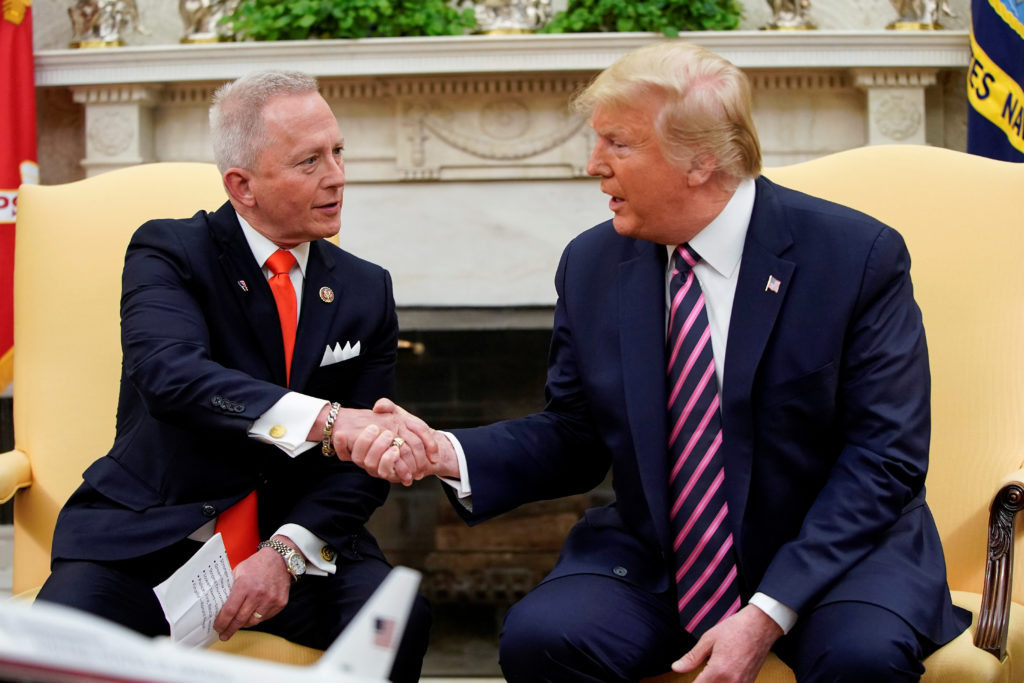 U.S. President Donald Trump shakes hands with U.S. Representative Jeff Van Drew, a Democratic lawmaker who opposed his party's move to impeach Trump, after Van Drew announced he was becoming a Republican in the Oval Office of the White House in Washington, U.S., December 19, 2019. Photo by REUTERS/Joshua Roberts