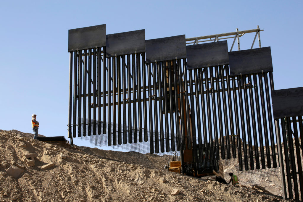 A construction crew works on a bollard-type private border wall, crowd-funded by We Build The Wall group at Sunland Park, ...