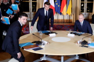 Ukrainian President Volodymyr Zelenskiy sits down with French President Emmanuel Macron and Russian President Vladimir Putin for a working session at the Elysee Palace, in Paris, France December 9, 2019. The Russian and Ukrainian presidents are meeting for the first time at the summit to find a way to end the five years of fighting in eastern Ukraine. Photo by Thibault Camus/Pool via REUTERS