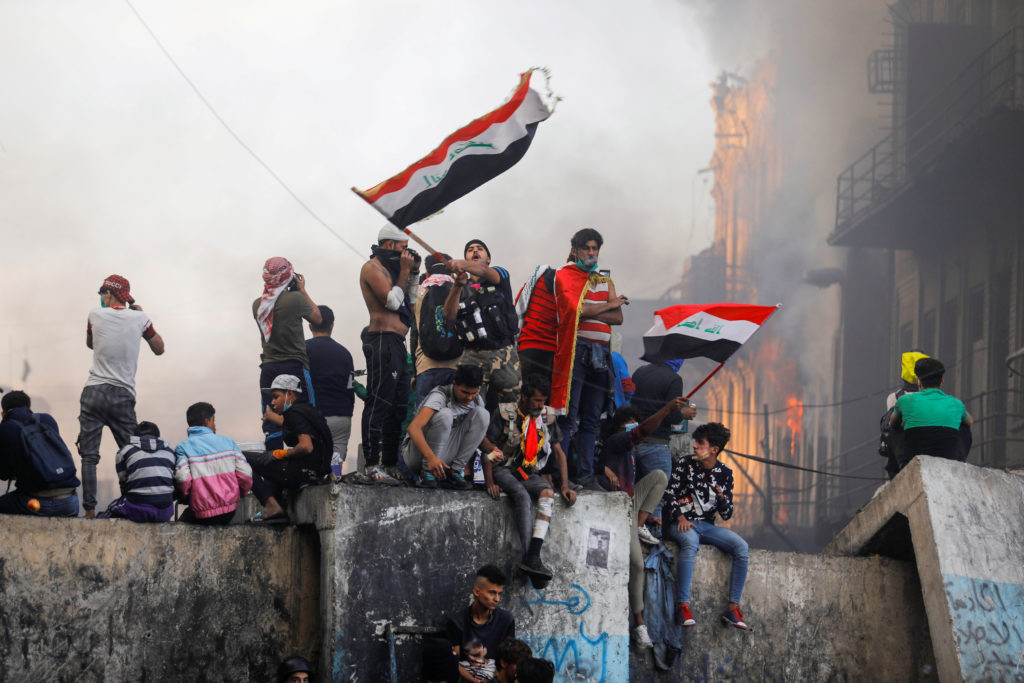 A demonstrator carries the Iraqi flag during ongoing anti-government protests, in Baghdad on November 30. Photo by Khalid ...