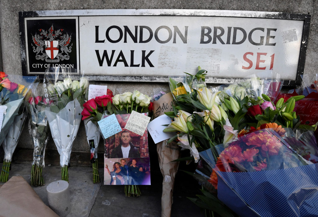 Messages of condolence and floral tributes, including a photograph of victim Jack Merritt, are seen near the scene of a stabbing on London Bridge. Photo by Toby Melville/Reuters