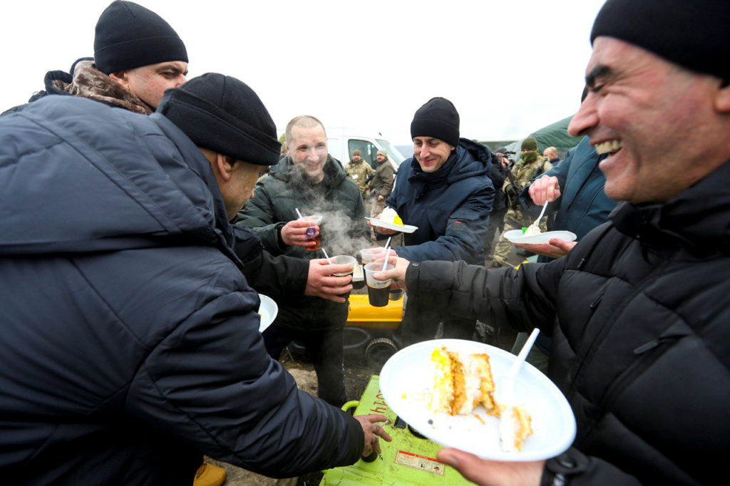Ukrainian citizens have meals after they were exchanged during a prisoners of war the swap. Photo handout via Ukrainian Presidential Press Service