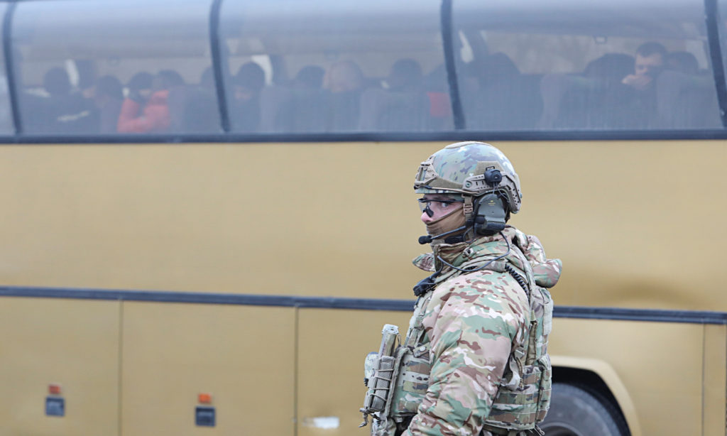 A Ukrainian serviceman stands guard near a bus for pro-Russian rebels during the exchange of prisoners of war near the Mayorsk checkpoint in the Donetsk region of Ukraine on December 29, 2019. Photo by Vyacheslav Madiyevskyy/Reuters