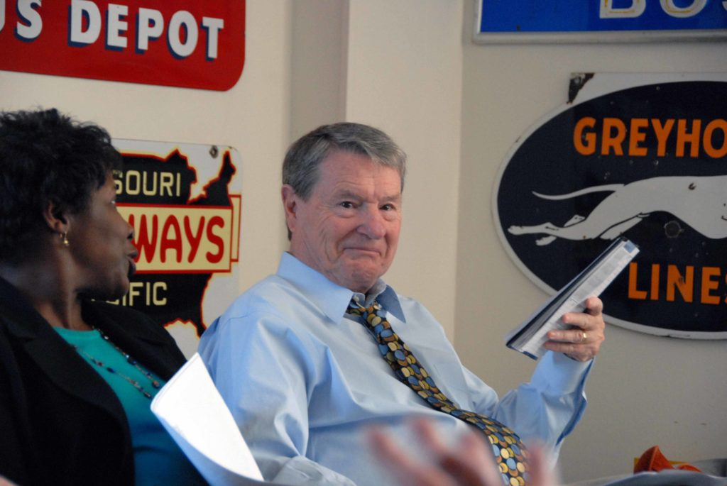 Jim Lehrer sits beside Gwen Ifill during an editorial meeting in his office, which was decorated with bus memorabilia. Photo by Daniel Sagalyn