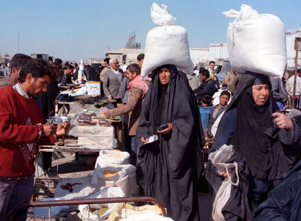 Iraqis shop at an outdoor market in Baghdad for essential foods February 2, 1997. At the time, Iraq's Central Bank governor Isam Hweish said that despite U.N. sanctions, imposed on Baghdad for its 1990 invasion of Kuwait, trade across its porous borders with Jordan, Turkey and Iran helped maintain a supply of some necessary goods. Photo via Reuters