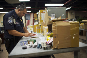 FILE PHOTO: U.S. Customs and Border Protection officer Boris Sapozhnikov looks at counterfeit drugs seized by the agency at its offices at John F. Kennedy Airport in New York August 15, 2012.