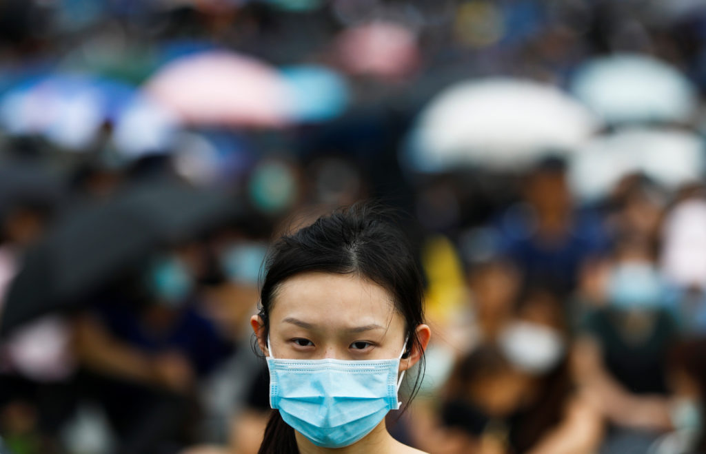 A protester covers her face with a mask during a general strike at …