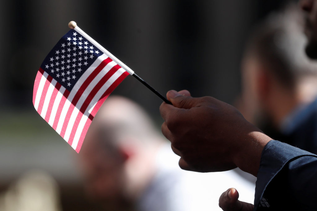 A citizenship candidate holds a flag during the U.S. Citizenship and Immigration Services (USCIS) naturalization ceremony at Rockefeller Plaza in New York City, U.S., September 17, 2019. Photo by Shannon Stapleton/Reuters