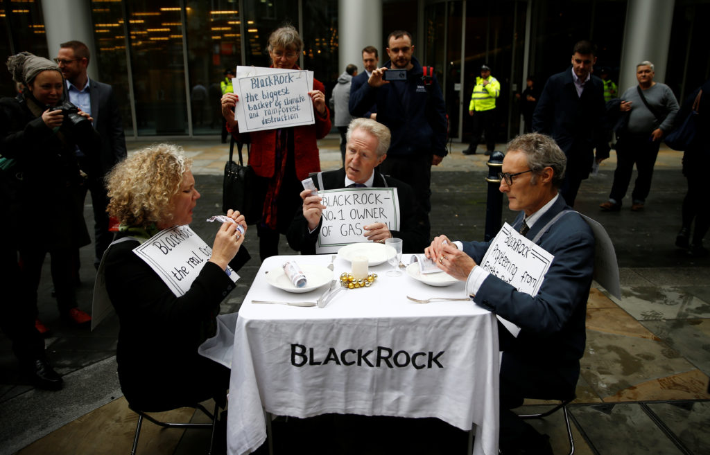 Protesters eat fake money outside the BlackRock office during an Extinction Rebellion demonstration in the City of London, Britain October 14, 2019.  Photo by Henry Nicholls/Reuters