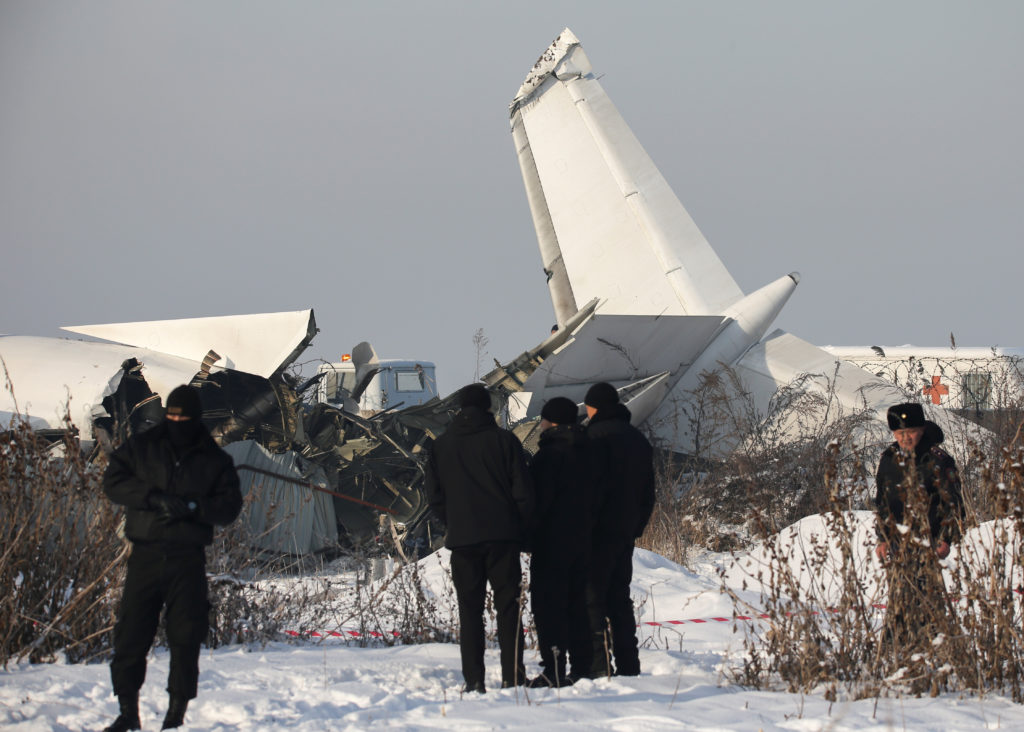Emergency and security personnel are seen at the site of a plane crash near Almaty, Kazakhstan, December 27, 2019. Photo b...