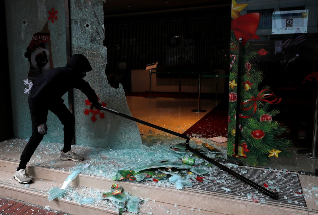 An anti-government protester vandalizes a bureau of the China Life Insurance Company during demonstration on New Year's Day, to call for better governance and democratic reforms in Hong Kong, China, January 1, 2020. Photo by Tyrone Siu/Reuters