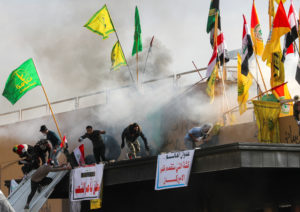 Protesters and militia fighters run away from tear gas thrown by U.S. Embassy security men, during a protest to condemn air strikes on bases belonging to Hashd al-Shaabi (paramilitary forces), outside the embassy in Baghdad, Iraq January 1, 2020. Photo by Thaier al-Sudani/Reuters