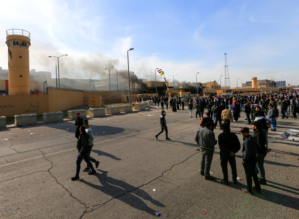 Protesters and militia fighters gather to condemn airstrikes on bases belonging to Hashd al-Shaabi (paramilitary forces), outside the U.S. Embassy in Baghdad, Iraq January 1, 2020. Photo by Thaier al-Sudani/Reuters