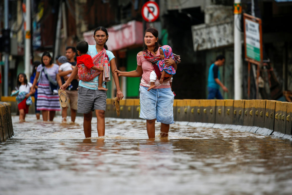 Women carrying their children walk accross the floodwaters at the J…