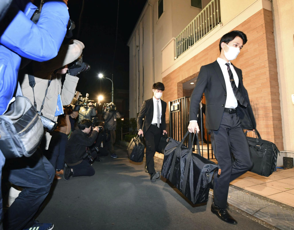Officials from the Tokyo District Public Prosecutors Office carry b…