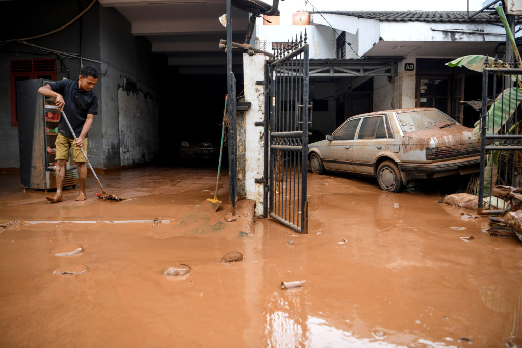 A man cleans up the clay after floods hit a residential area in Bin…
