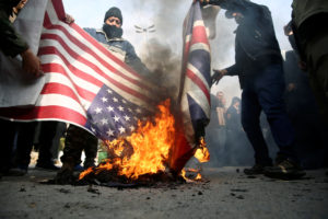 Demonstrators burn the U.S. and British flags during a protest against the assassination of the Iranian Major-General Qassem Soleimani, head of the elite Quds Force, and Iraqi militia commander Abu Mahdi al-Muhandis who were killed in an air strike in Baghdad airport, in Tehran, Iran January 3, 2020. WANA (West Asia News Agency)/Nazanin Tabatabaee via Reuters