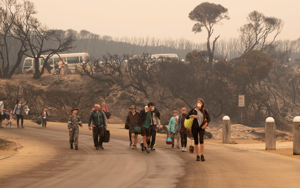 An image obtained on January 3, 2020, shows bushfire evacuees walking down to the beach to board vessels and be ferried ou...