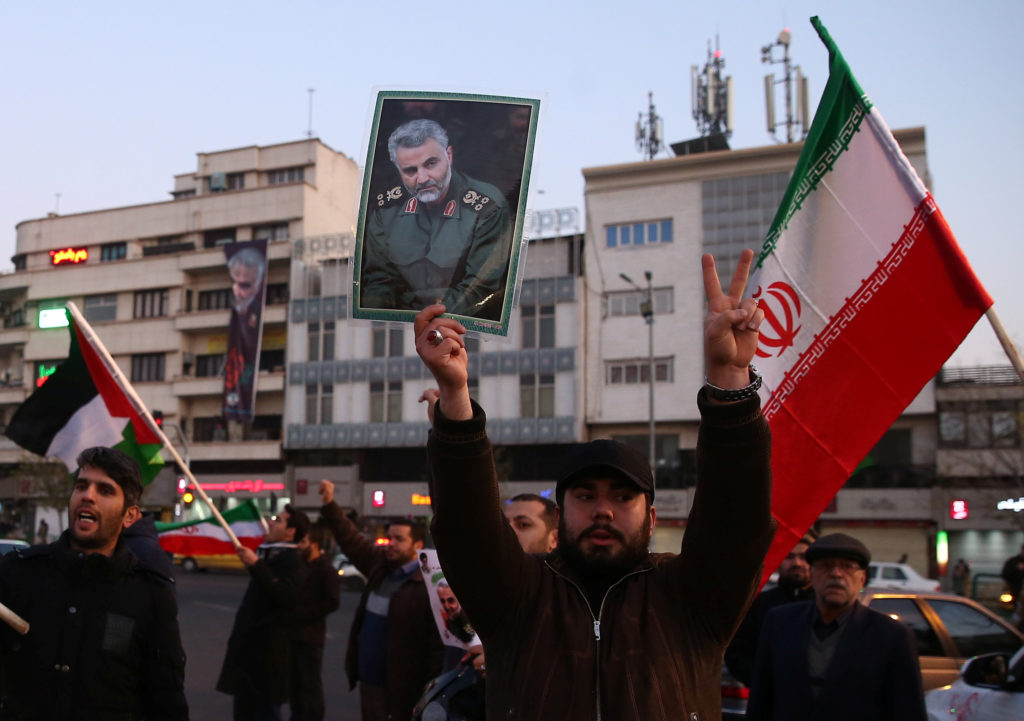 A man holds a picture of late Iranian Major-General Qassem Soleimani, as people celebrate in the street after Iran launched missiles at U.S.-led forces in Iraq, in Tehran, Iran January 8, 2020. Nazanin Tabatabaee/WANA (West Asia News Agency) via Reuters