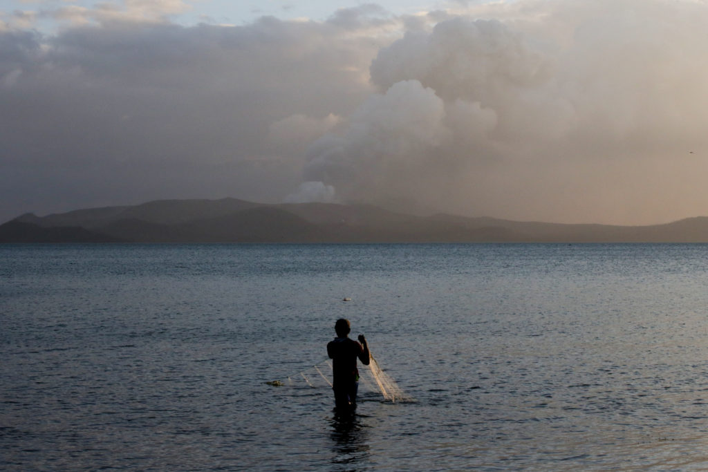 A man catches fish as the Taal Volcano continues to erupt in Talisa…